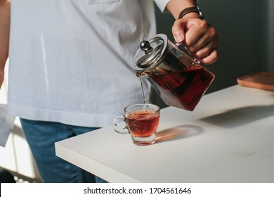 Close up man pouring hot tea from teapot  into small glass near window.Process brewing tea,tea ceremony,Cup of freshly brewed yellow or green herb tea,warm soft light, dark mood.Liquid movement in cup