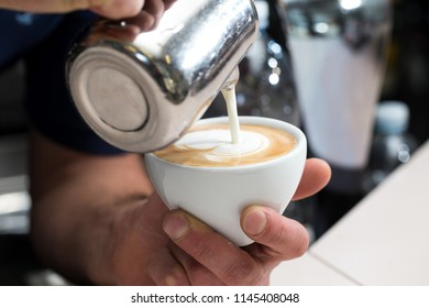 close up of a man pouring milk into a cup of coffee, he is making a cappuccino