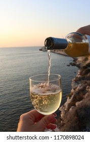 Close up of a man pouring white wine in a glas with a beautiful scenery of Bozcaada island at sunset in the background.