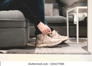 close up man put on casual sneakers and tie shoelaces on the couch and carpet