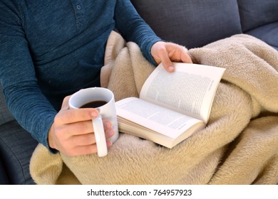 close up - Man is reading a book on the sofa while drinking a coffee