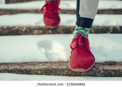 Close Up of a man in red sneakers walking down the snowy stairs