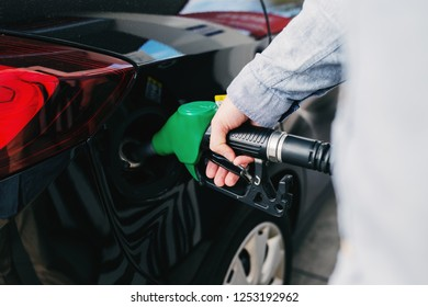 Close up of man refilling tank on his car on the gas station.