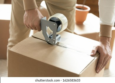Close up of man sealing packing cardboard box with scotch tape moving or relocating, Caucasian husband roll carton package personal belongings using adhesive cellotape, relocation service concept