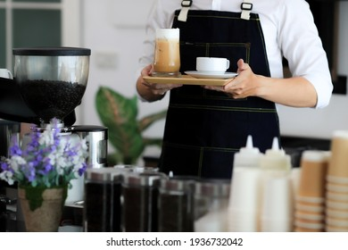 Close up of man serving coffee and tea while standing in coffee shop. Focus on male hands placing a cup of coffee on counter. Concept cafe shop coffee