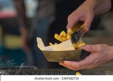 close up of man serving fish and chips into greaseproof paper and box