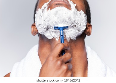 Close up of man shaving. Close up of young African man shaving his face while standing against grey background