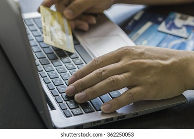 Close Up Of A Man Shopping Online Using Laptop With Credit Card,male hands holding credit card typing numbers on computer keyboard while sitting at home at the wooden table,selective focus