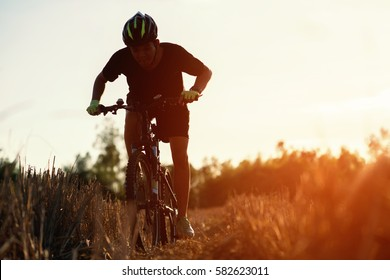 Close up man, silhouette young man on bike in the nature at sunset. Shot with sunflare