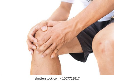 Close up of a man sitting and holding his knee in pain due to injury on white background
