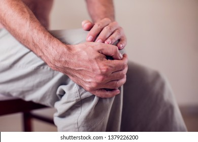 Close up of a man sitting and holding his knee in pain due to injury on white background. Healthcare, medicine and people concept