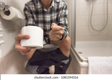 Close up of Man sitting in toilet feeling unhappy and holds toilet paper roll diarrhea constipation,Health concept