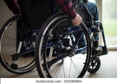 Close Up Of Man Sitting In Wheelchair At Home By Window