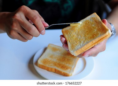 Close up of a man spreading butter on toast
