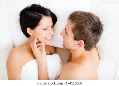 Close up of man stroking woman lying in bed, top view. Concept of love and affection