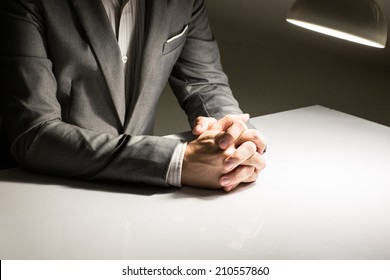 close up of a man in a suit with his hands clasped in front