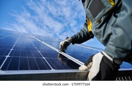 Close up of man technician in work gloves installing stand-alone photovoltaic solar panel system under beautiful blue sky with clouds. Concept of alternative energy and power sustainable resources.