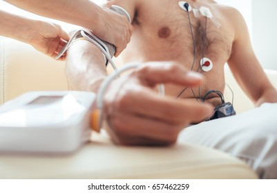 Close up man tested with Holter monitor hand with Sphygmomanometer
