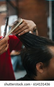 Close up of man that getting haircut by hairdresser with scissors and comb while sitting in chair. Barber shop