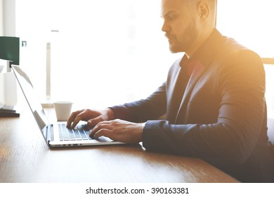 Close up of man trader is analyzing financial market via laptop computer, while is sitting in modern office interior. Male skilled accountant is checking the validity of the operation  via net-book