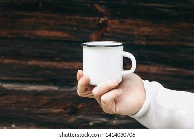 Close up of man travelers hand holding metal mug with hot drink. Outdoor tea, coffee relax time. Mockup of white enamel cup.  Adventure, travel, tourism and camping concept. Blurred wooden background.