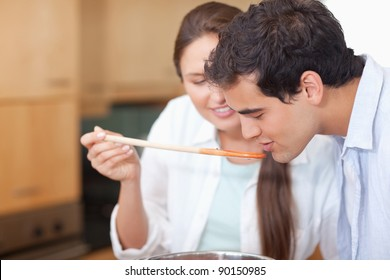 Close up of a man trying his wife's sauce in their kitchen