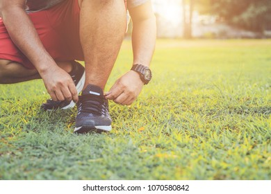 Close up man tying rope on his sports shoe. Preparing for run in the park in sunset time. Exercise and healthy concept use