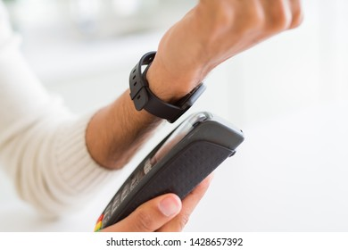Close up of man using electronic watch as payment metod. Swiping on contactless point of sale dataphone