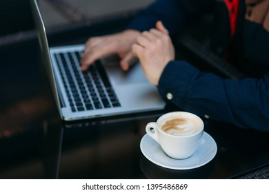 Close up of man using laptop on the table. Cappuchino on the glass table
