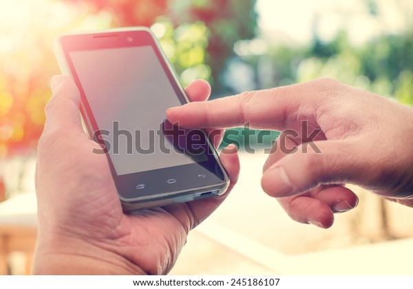 Close up of a man using mobile smart phone outdoor,  nature background. (vintage color tone)