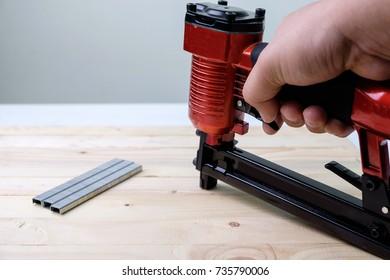 Close up a man using pneumatic nailer gun on wooden background.