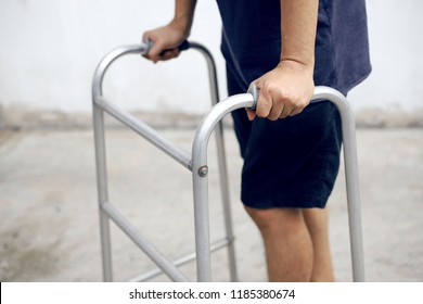 Close up of man using a walker for walk support.