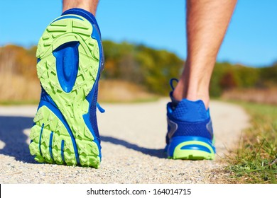 Close up of man walking on nature trail near forest preserve. Color image, copy space, male walking outside on a beautiful day in nature.Horizontal