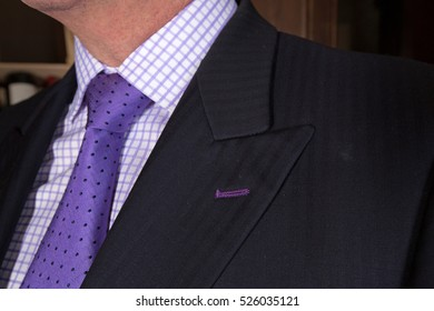 Close up of a man wearing a purple tie and checked shirt with dark grey suit jacket
