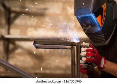 Close up of man, wearing in special protective gloves and welding mask, brewing metal with welding machine in workshop, sparks fly in the sides. Welder wearing in black T-shirt working at workplace.