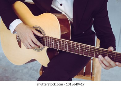 Close - up man wearing a suit is sitting play acoustic guitar in a rehearsal room.