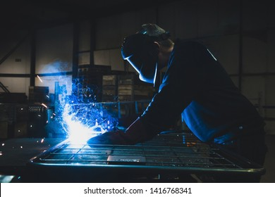Close up of a man welding in a dark factory that causes sparks and light.