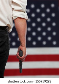 Close up of man in white shirt & dark trousers carrying handgun with out of focus cropped US flag in the background
