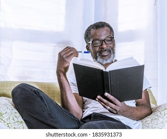 Close up of a man in white shirt reading a book