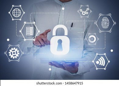Close up of man in white shirt using tablet computer with double exposure of cyber security interface. Concept of data protection. Toned image