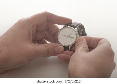 Close up of a man winding his wrist watch