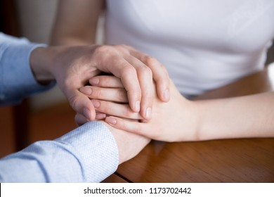 Close up of man and woman holding hands showing love and empathy, couple reconciled give support or comfort to spouse, male caress female expressing understanding and care. Good relationships concept