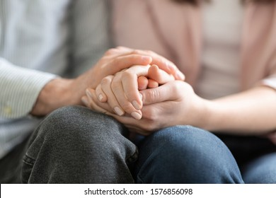 Close up of man and woman holding hands, giving psychological support