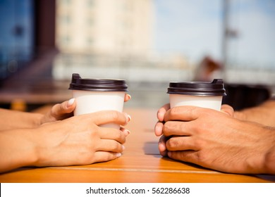 Close up of man and woman holding two cups of coffee