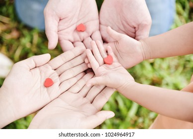Close up Man, Woman and Kid hands holding red hearts together on grass background at park outdoor. Family. Love.