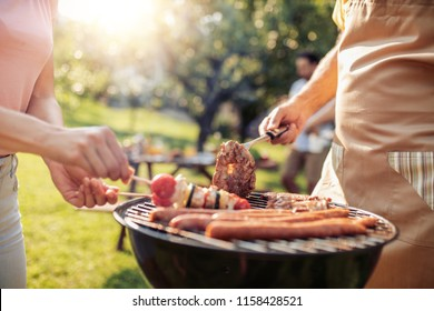 Close up of a man and woman making barbecue together.