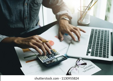 Close up a man working about financial with calculator at his office to calculate expenses, Accountigng concept