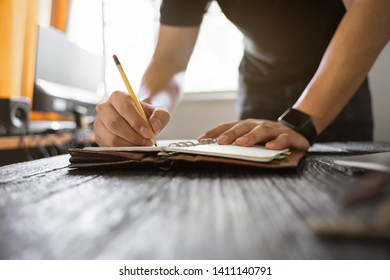 Close up of a man working with writing on a book.