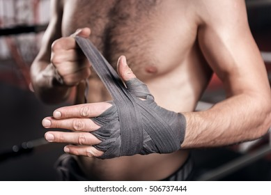 Close up of man wrapping hand in boxing tape