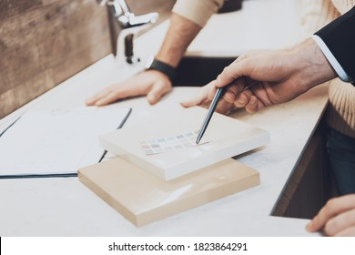 Close up manager in suit is showing different materials and color swatches to couple clients in kitchen store.The seller shows the strength of materials for buyers.  - Shutterstock ID 1823864291